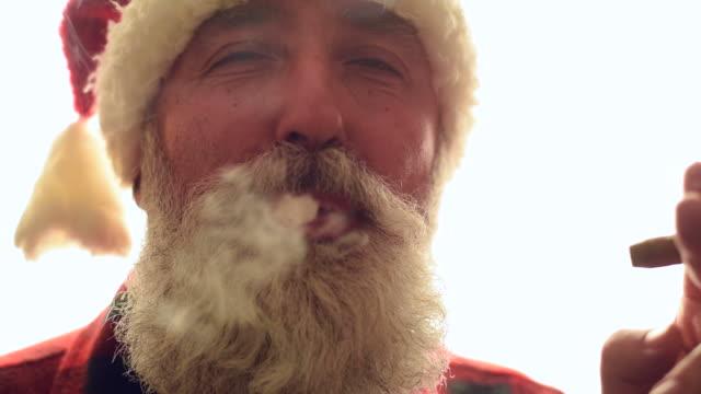 adult senior man in santa hat smoking a cigar on a white background. - santa hat stock videos & royalty-free footage