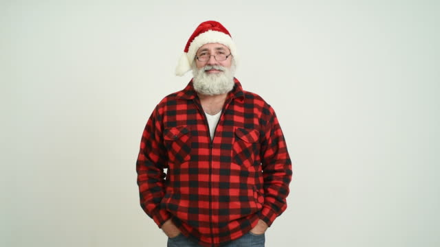 adult senior man looking smiling at the camera in the santa claus hat on a grey background - santa hat stock videos & royalty-free footage