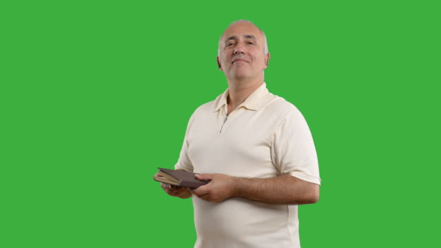 adult senior man reading a book on the green screen - white shirt stock videos & royalty-free footage