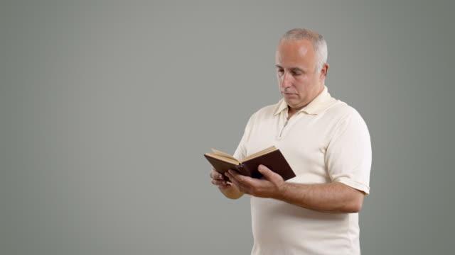 vídeos y material grabado en eventos de stock de adulto hombre mayor leyendo un libro en la pantalla gris - altos cargos directivos