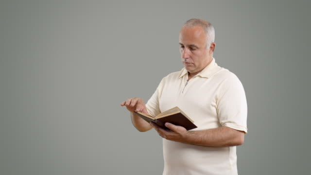 adult senior man reading a book on the grey screen - white shirt stock videos & royalty-free footage