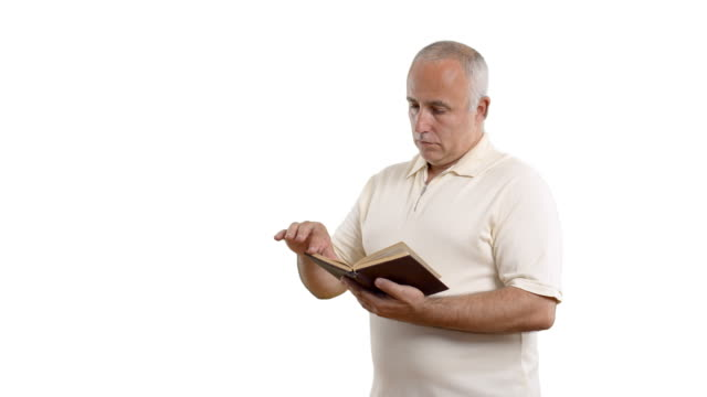 adult senior man reading a book on the white screen - white shirt stock videos & royalty-free footage