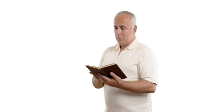 vídeos y material grabado en eventos de stock de adulto hombre mayor leyendo un libro blanco sobre la pantalla - camisa blanca