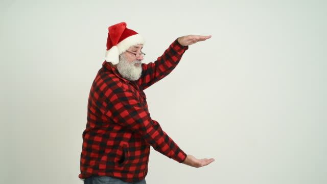 adult senior man showing a copy space and showing the thumb in the santa claus hat on a grey background - santa hat stock videos & royalty-free footage