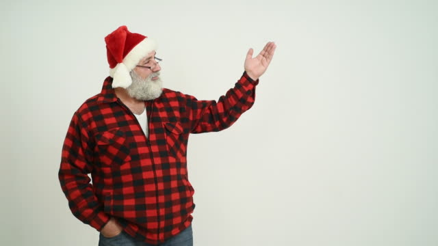 adult senior man showing a copy space in the santa claus hat on a grey background - santa hat stock videos & royalty-free footage