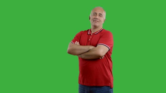 vídeos de stock e filmes b-roll de adulto homem idoso mostrando uma espaço para texto em fundo verde - 50 54 anos