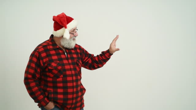 adult senior man showing a four copy space in the santa claus hat on a grey background - santa hat stock videos & royalty-free footage