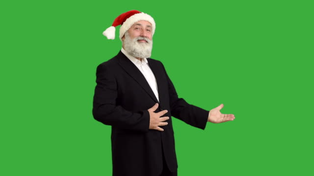 adult senior man shows copy space  in a hat santa claus  on a green background - santa hat stock videos & royalty-free footage