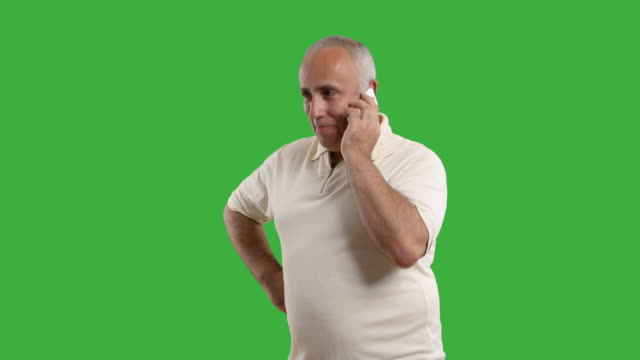 Adult senior man talking on the phone on green background