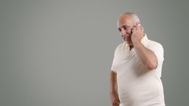 vídeos y material grabado en eventos de stock de adulta senior hombre hablando por teléfono en fondo blanco - altos cargos directivos