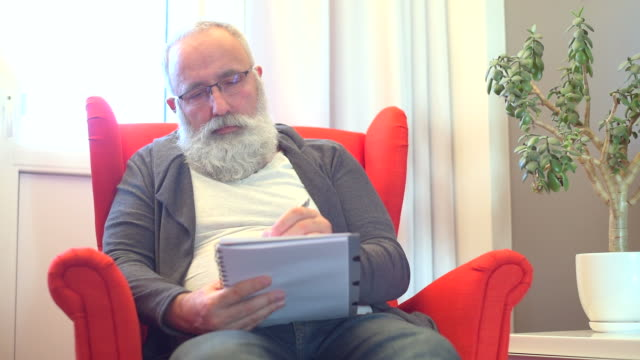 adult senior man with a white beard draws in a notebook - red pen stock videos & royalty-free footage