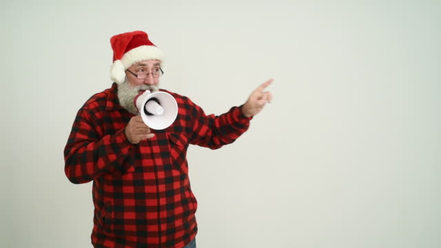adult senior man with megaphone showing a copy space in the santa claus hat on a grey background - santa hat stock videos & royalty-free footage