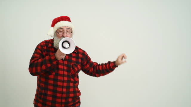 adult senior man with megaphone showing a four copy space in the santa claus hat on a grey background - santa hat stock videos & royalty-free footage