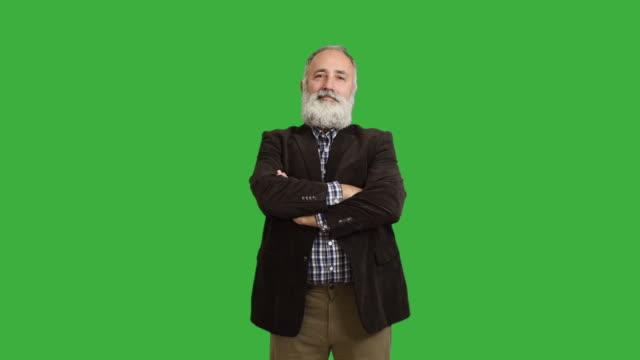 Adulto sorridente uomo anziano guarda nella macchina fotografica e attraversa le sue braccia su uno sfondo verde