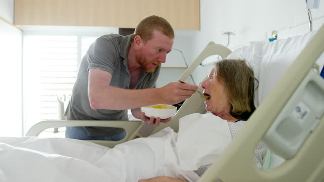 adult son feeds elderly mother in hospital - community care stock videos & royalty-free footage
