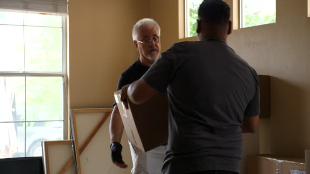 stockvideo's en b-roll-footage met r/f ms adult son helping senior father in law stack boxes in new home while moving - werkende bejaarden