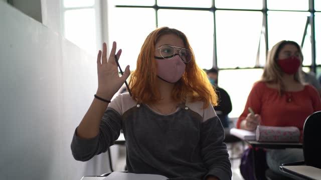 vídeos de stock, filmes e b-roll de estudante adulto cursando a aula - usando máscara facial - de braço levantado