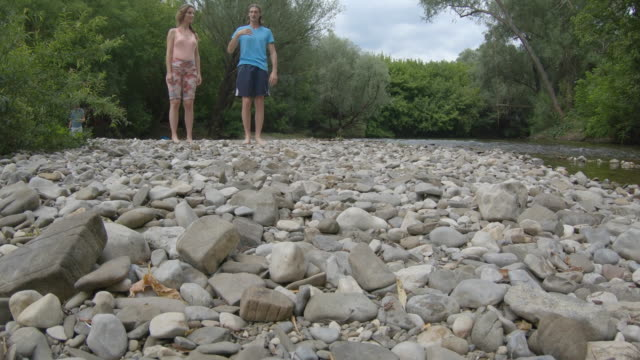 adult woman and man standing on pebble riverbank barefoot - riverbank stock videos & royalty-free footage