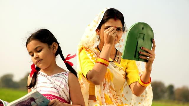 adult woman applying bindi on her face, haryana, india - bindi stock videos and b-roll footage