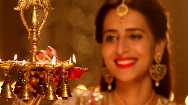 vidéos et rushes de adult woman burning oil lamp in diwali festival, delhi, india - rouge à lèvres rouge