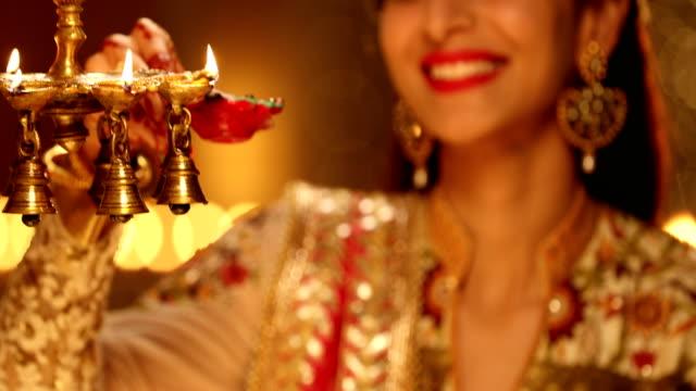 adult woman burning oil lamp in diwali festival, delhi, india - 盆点の映像素材/bロール