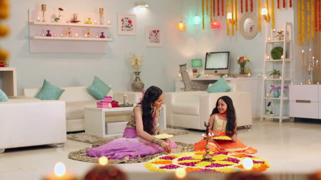 Adult woman celebrating diwali festival with her daughter