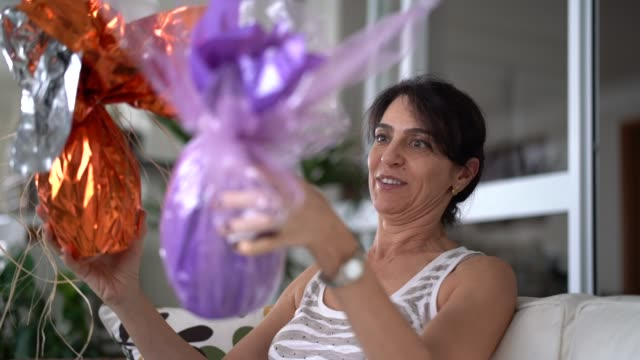 adult woman celebrating the brazilian easter with chocolate eggs - only mature women stock videos & royalty-free footage