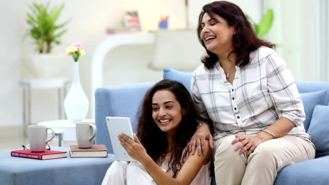 Adult woman chatting on digital tablet with her daughter, Delhi, India