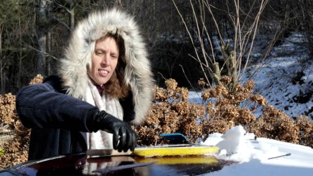 大人の女性が車の屋根に雪の清掃 - 掃く点の映像素材/bロール