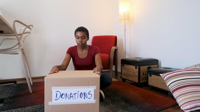 vídeos y material grabado en eventos de stock de mujer adulta que cierra caja de cartón para donación. - sólo mujeres jóvenes