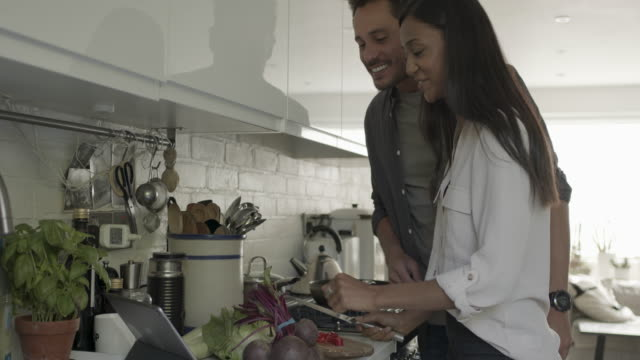 adult woman cooking at home looking at recipe on digital tablet - spanish and portuguese ethnicity stock videos & royalty-free footage