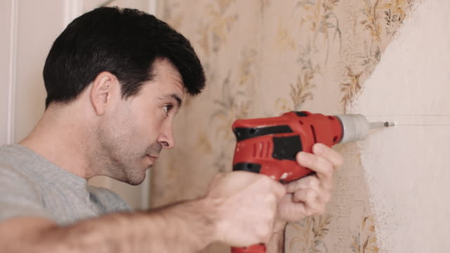 vídeos de stock, filmes e b-roll de adult woman drilling into the wall of new home - parede