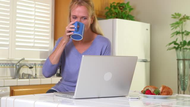 vídeos de stock, filmes e b-roll de adult woman drinking morning coffee while using computer - só uma mulher madura