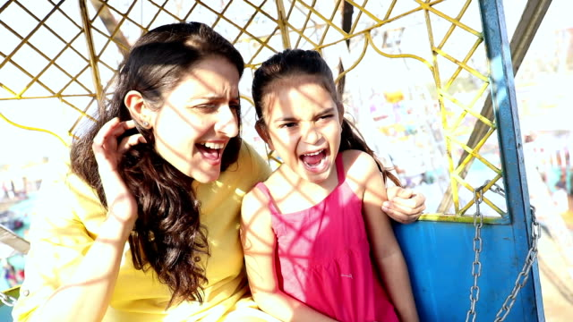 adult woman enjoying ferris wheel with her daughter at suraj kund fair, haryana, india - haryana stock-videos und b-roll-filmmaterial