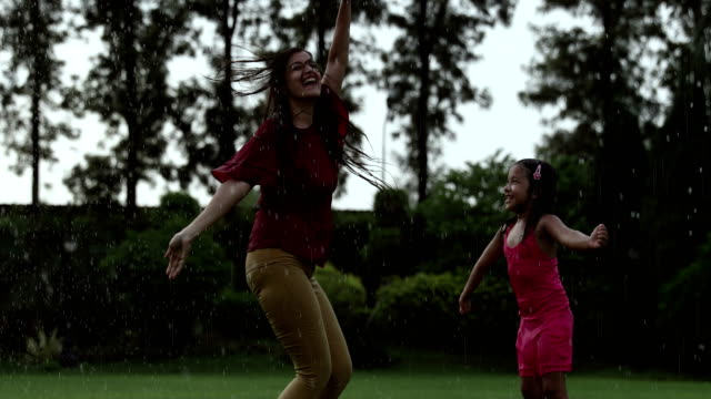 adult woman enjoying in the rain with her daughter, delhi, india - shower videos stock videos & royalty-free footage