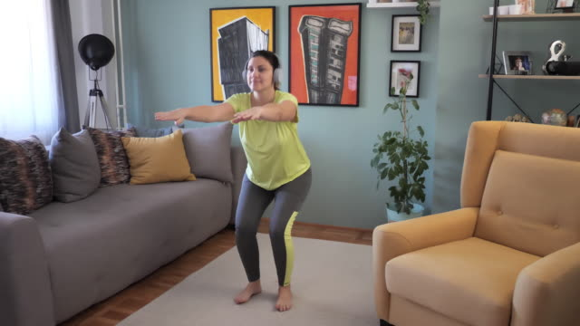 adult woman exercising at home during quarantine - crouching and strength exercises - epidemiology stock videos & royalty-free footage