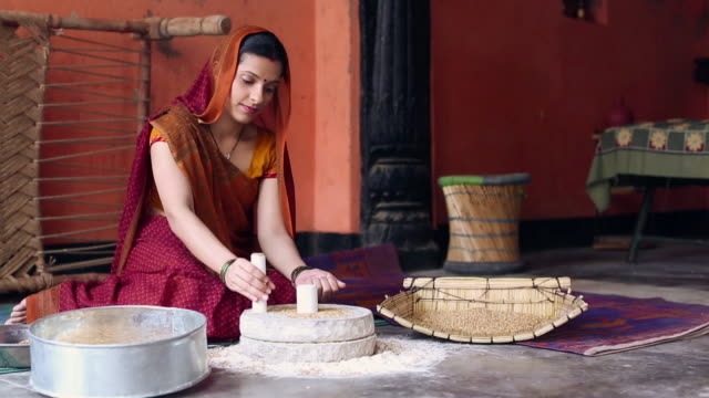 Adult woman grinding wheat on grinding stone, Delhi, India