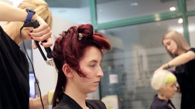 adult woman hairdresser curling hair of a young woman - film montage stock videos & royalty-free footage