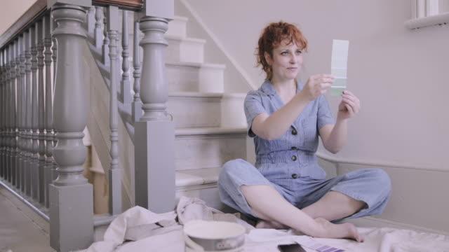vídeos y material grabado en eventos de stock de adult woman in new home looking at color paint swatches - reforma