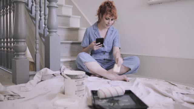 vídeos y material grabado en eventos de stock de adult woman in new home looking at decorating ideas on smart phone - reforma
