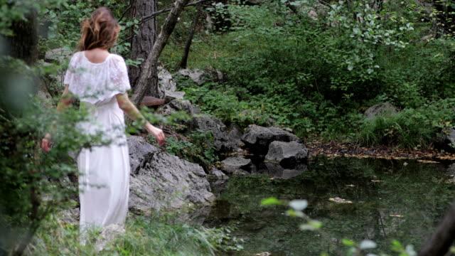 stockvideo's en b-roll-footage met volwassen vrouw in witte jurk ontspannen door een klein meer in bos - vijver