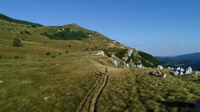 adult woman jogging on top of nanos plateau in slovenia - slovenia stock videos & royalty-free footage
