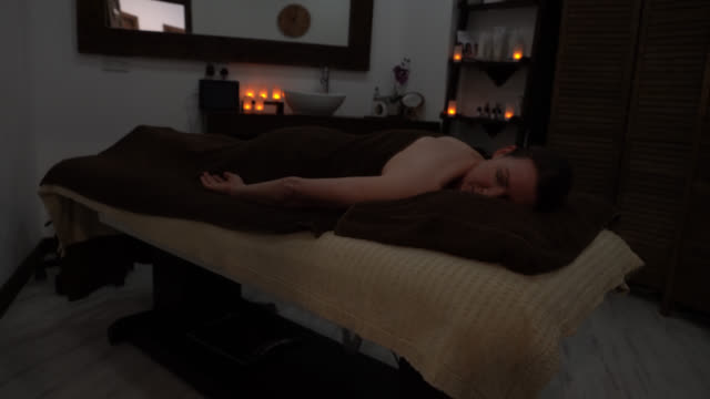 adult woman lying down on front at the spa relaxing after a back massage in the spa - massage table stock videos & royalty-free footage