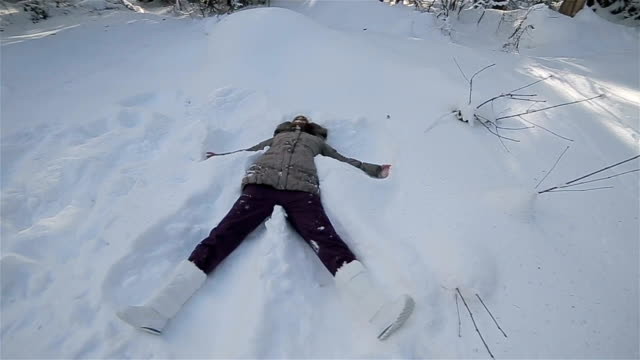 Adult woman makes snow angel,camera stabilization shoot