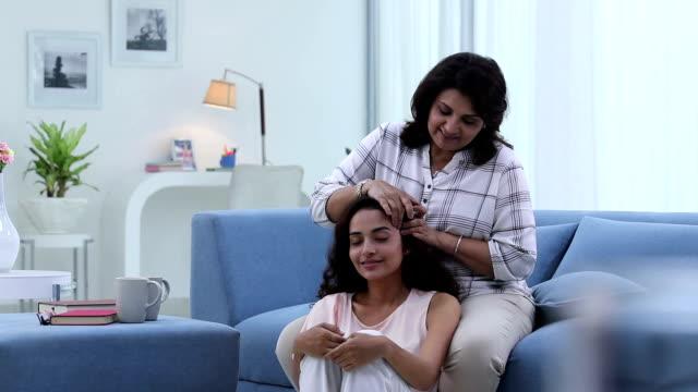 adult woman massaging her daughter hair, delhi, india - 床に座る点の映像素材/bロール