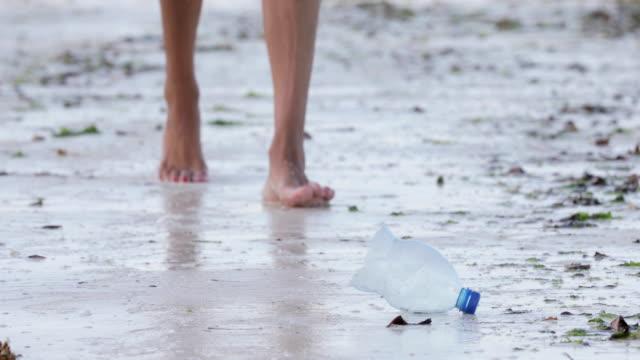 大人の女性のビーチでペットボトルを拾って - ウォーターボトル点の映像素材/bロール