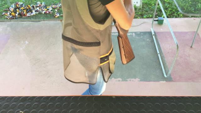 stockvideo's en b-roll-footage met volwassen vrouw het oppakken van shotgun op shooting range - jachtgeweer