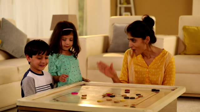 adult woman playing carrom with her kids at home, delhi, india - familie mit zwei kindern stock-videos und b-roll-filmmaterial