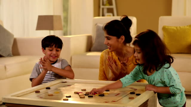 adult woman playing carrom with her kids at home, delhi, india - carrom stock videos & royalty-free footage