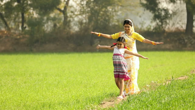 Adult woman playing with her daughter in the farm, Haryana, India